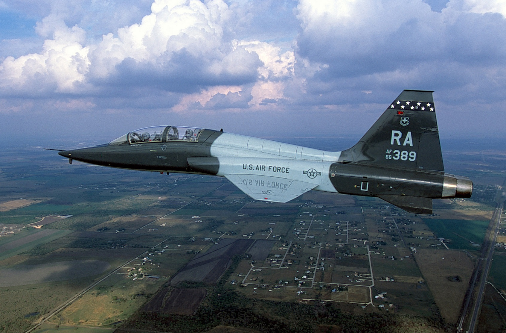 Air-to-air left side view of an USAF T-38 Talon aircraft from 560th Flying Training Squadron, Randolph AFB, TX flying over the Texas countryside.